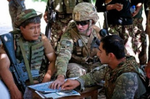 A U.S. Army captain, center, speaks with an Afghan army officer, left, during a patrol break June 15 in Afghanistan's Najgarhar province. (Sgt. Margaret Taylor/U.S. Army)