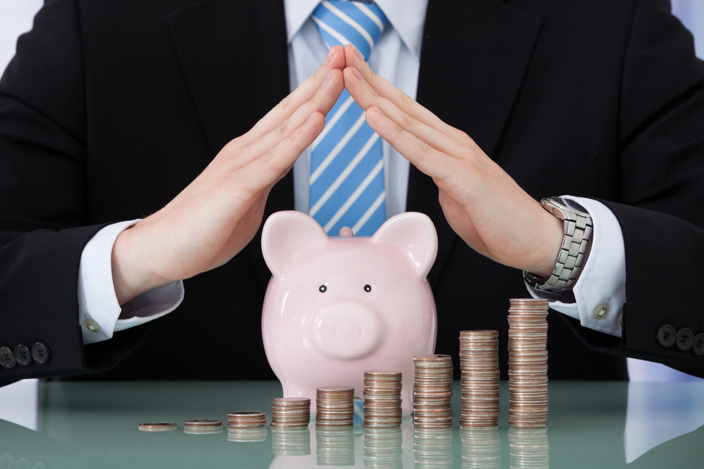 Midsection of young businessman sheltering piggybank and coin stacks at office desk